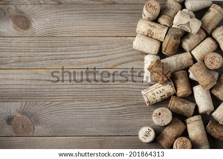 Heap of assorted wine corks on wooden background. - stock photo