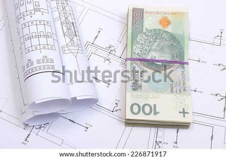 Heap of banknotes and rolls of electrical diagrams lying on construction drawing of house, concept of building house, drawings for the projects engineer jobs - stock photo