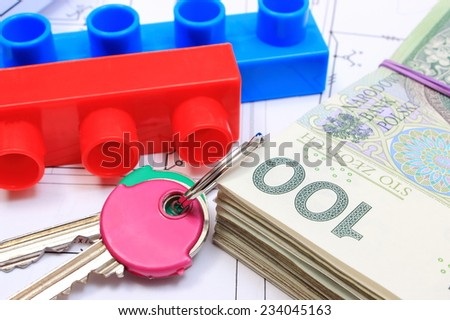Heap of banknotes, home keys and plastic building blocks lying on construction drawing of house, concept of building house, drawings for the projects - stock photo