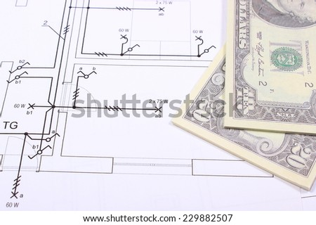 Heap of banknotes lying on electrical construction drawing of house, concept of building house - stock photo