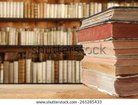 heap of books with book shelf in the background - stock photo