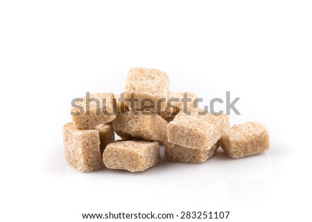 Heap of brown sugar cubes isolated on a white background - stock photo