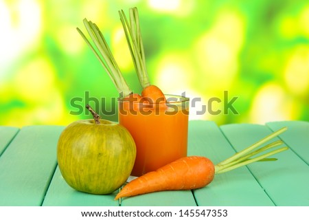 Heap of carrots and green apple, glass of juice, on color wooden  table on bright background - stock photo