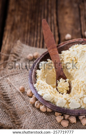 Heap of Chick Pea flour on an old wooden table - stock photo