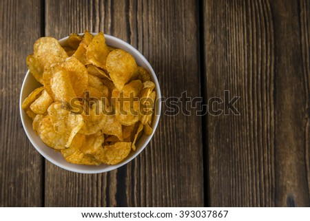 Heap of Chilli Potato Chips (selective focus) on an old wooden table - stock photo