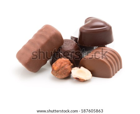 Heap of chocolate candies and nuts isolated on white background - stock photo