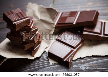 Heap of chocolate with rustic packing paper on wooden table - stock photo