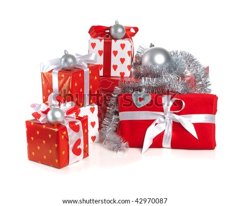 heap of Christmas red gifts decorated with silver balls and tinsel on white background - stock photo