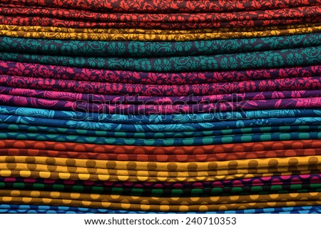Heap of cloth fabrics at a local market in India. Close up . - stock photo