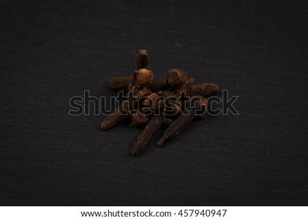 Heap of clove spice on dark stone plate background - stock photo