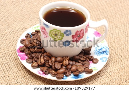 Heap of coffee grains and cup of hot beverage, colorful cup of coffee - stock photo