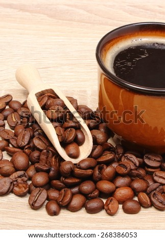Heap of coffee grains and cup of hot beverage, cup of coffee. Isolated on wooden background - stock photo