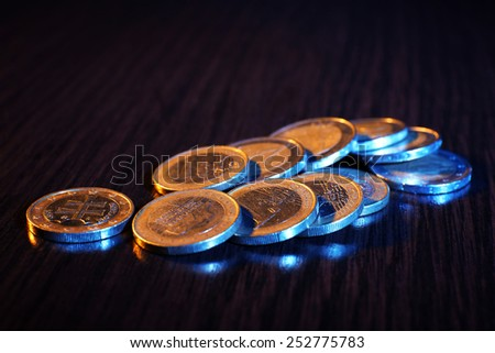 Heap of coins on wooden table background - stock photo