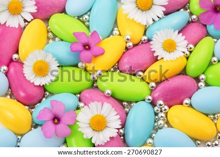 heap of colored sugar coated almonds and wildflowers - stock photo