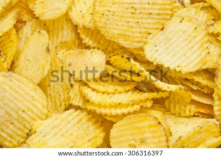 heap of corrugated tasty potato chips closeup - stock photo