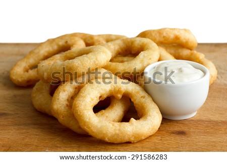 Heap of deep fried onion or calamari rings with garlic mayonnaise dip on wood board. - stock photo