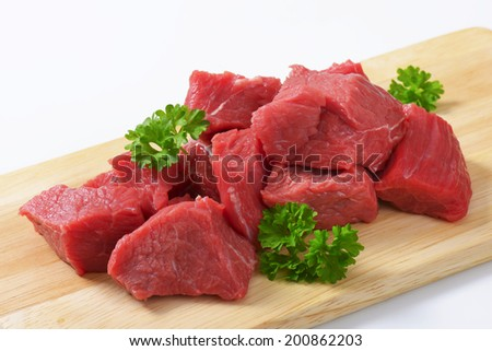 heap of diced beef meat with pieces of parsley, served on the wooden cutting board  - stock photo