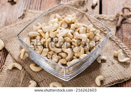 Heap of dried Cashew Nuts (close-up shot) on rustic background - stock photo