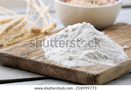 Heap of flour on cutting board with ears and grains in bowl on wooden table - stock photo