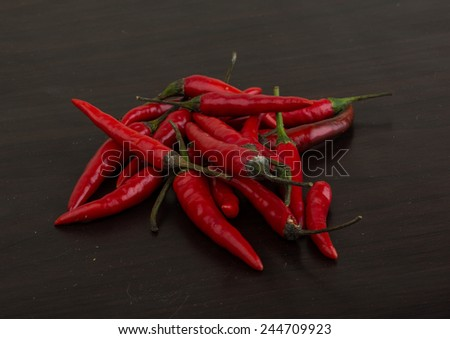 Heap of fresh chili peppers on the wood background - stock photo