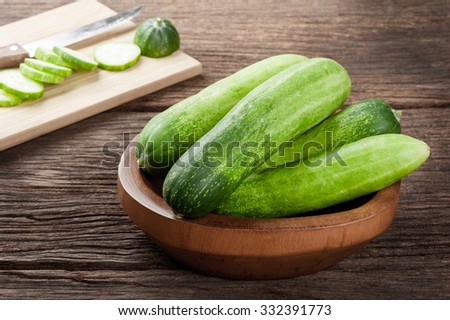 heap of fresh cucumbers in wooden bowl - stock photo
