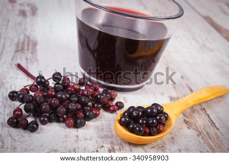 Heap of fresh elderberry with wooden spoon and glass of elderberry juice on old rustic wooden background, healthy nutrition, alternative medicine and therapy - stock photo