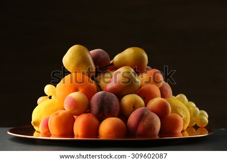 Heap of fresh fruits on dark background - stock photo