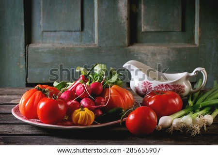 Heap of fresh ripe colorful vegetables tomatoes, chili peppers, green onion and bunch of radish on vintage plate and porcelain gravy boat over old wooden table. Dark rustic atmosphere - stock photo