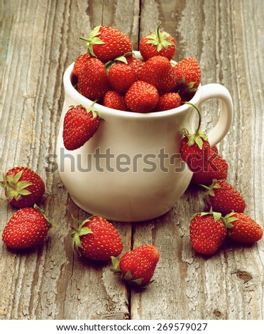 Heap of Fresh Ripe Forest Strawberries in White Bowl closeup on Rustic Wooden background. Retro Styled - stock photo