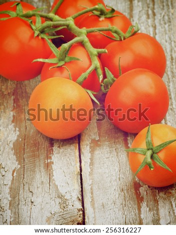 Heap of Fresh Ripe Red Cherry Tomatoes with Stem and Twigs on Rustic Wooden background. Retro Styled - stock photo