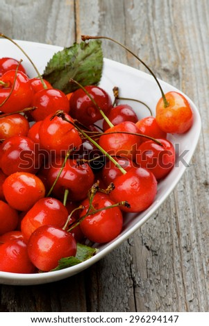 Heap of Fresh Ripe Sweet Maraschino Cherries in White Bowl Cross Section on Rustic Wooden background - stock photo