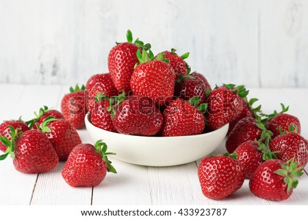 Heap of fresh strawberries in ceramic bowl on rustic white wooden background.  - stock photo