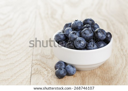 heap of fresh washed blueberries in white bowl on wood table - stock photo