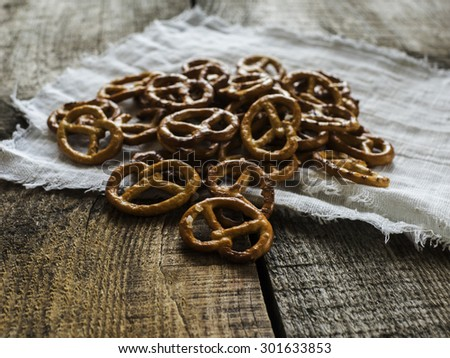 Heap of fresh Wheat salt pretzels on hessian linen fabric cloth and wooden table
