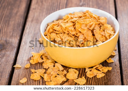 Heap of golden Cornflakes on a rustic wooden table - stock photo