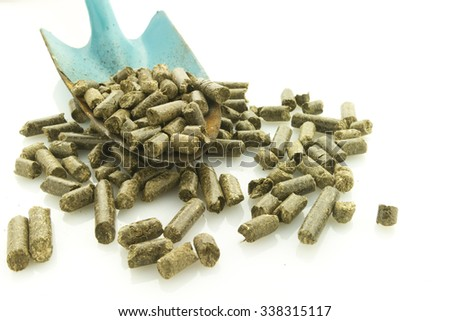 heap of grass pellets with shovel, symbol of renewable energy, isolated on white reflective background - stock photo