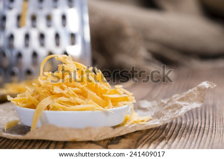 Heap of grated Cheddar Cheese (close-up shot) in rustic background - stock photo