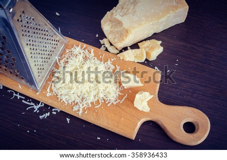 Heap of grated Parmesan cheese and metal grater on wooden board. Peace of Parmesan. - stock photo