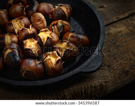 Heap of grilled edible chestnuts in cast iron skillet over dark wooden surface with textile napkin - stock photo