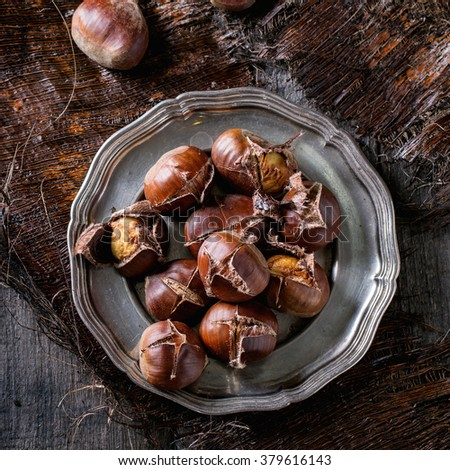 Heap of grilled edible chestnuts in vintage metal plate over dark palm crust. Top view.  Square image - stock photo