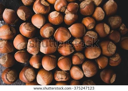 Heap of hazelnuts on a dark wood background. - stock photo