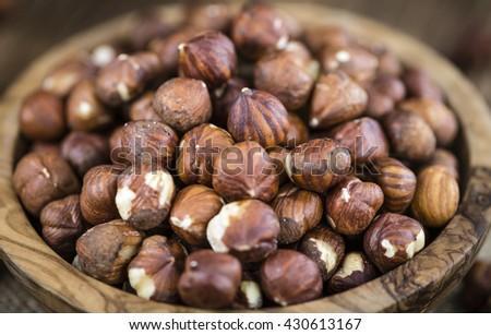 Heap of Hazelnuts (selective focus) on vintage background (close-up shot) - stock photo