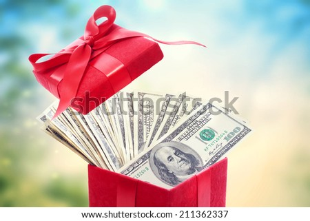 Heap of hundred dollar bills in a big red present box  - stock photo