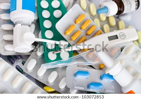 Heap of medical supplies, pills, tablets, capsules, nose drops and thermometer. - stock photo