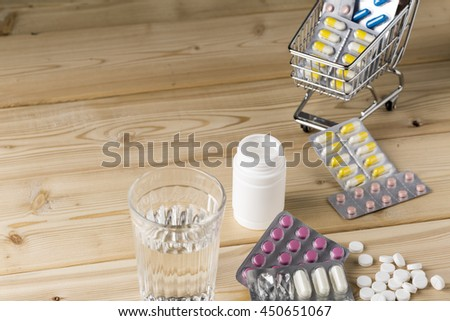 Heap of medicine colorful pills blister pack and water glass - stock photo