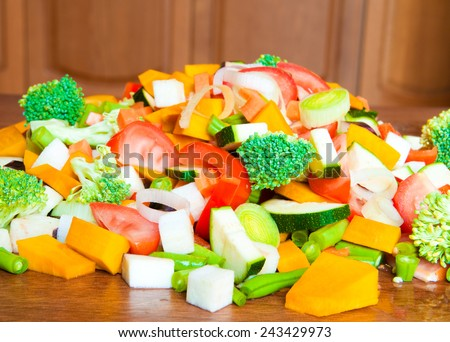Heap of mixed cut vegetables on wooden table - stock photo