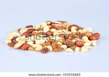 Heap of mixed nuts isolated on light blue background - stock photo