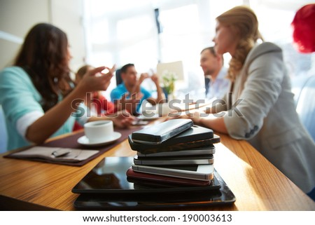 Heap of modern gadgets with group of friends on background - stock photo