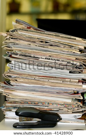 Heap of newspapers and magazines is in an office, disorder on a table. - stock photo