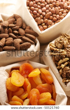 Heap of nuts and dried apricots in canvas bags. Focus on apricots. - stock photo